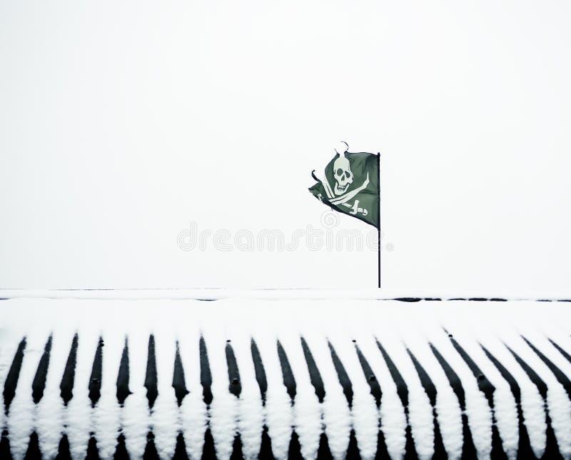 Una bandera de pirata negra desigual en un tejado nevado foto de archivo
