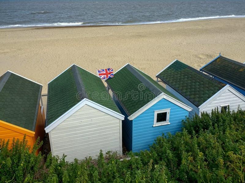 Una bandera del Union Jack vuela sobre chozas de la playa en Southwold, Suffolk, Inglaterra foto de archivo