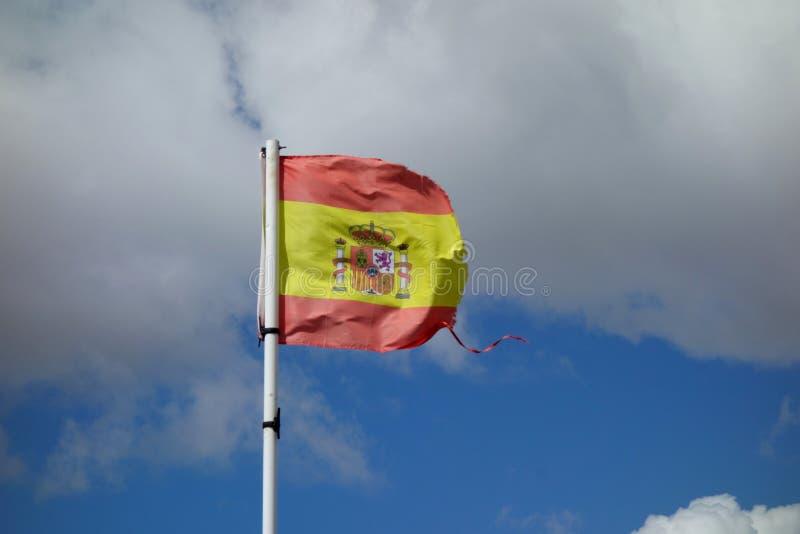 Una bandera española quebrada en un día ventoso, un día no-urbano de la escena foto de archivo