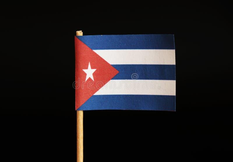 Una bandera nacional de Cuba en palillo y en fondo negro Cuba es famosa por criminalidad e importación y las drogas y cigarro de  foto de archivo libre de regalías