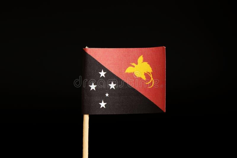 Una bandera oficial de Papúa Nueva Guinea en el palillo de madera en fondo negro Es isla estado y pertenece a Oceanía fotos de archivo