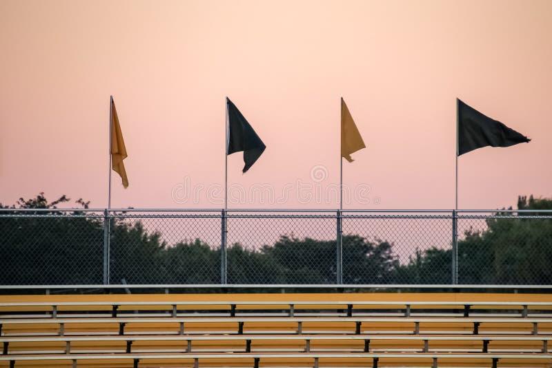 Una bandiera che vola fra 3 altre sopra i sedili dello stadio fotografia stock libera da diritti