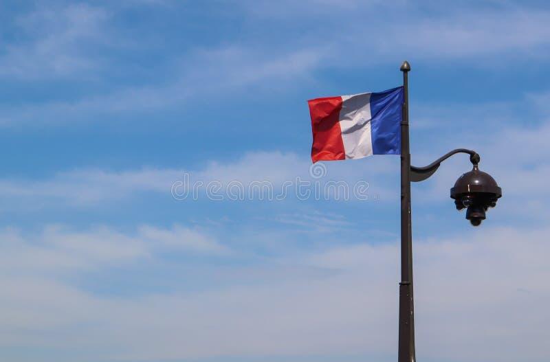 Una bandiera francese su un palo della luce a Parigi Francia Aprile 2019 immagine stock libera da diritti