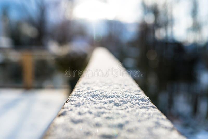 Una barandilla nevada, de madera en el balc?n con el foco selectivo En el fondo, los edificios borrosos y los ?rboles imagen de archivo