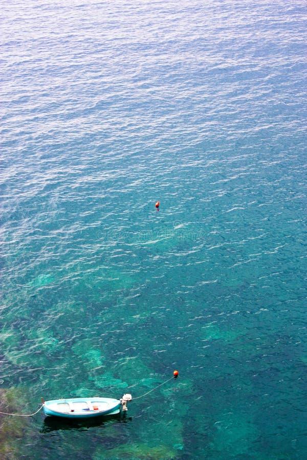 Una barca blu sola che oscilla sulle acque tranquille della spiaggia di Corniglia in Cinqueterre, Italia immagini stock libere da diritti