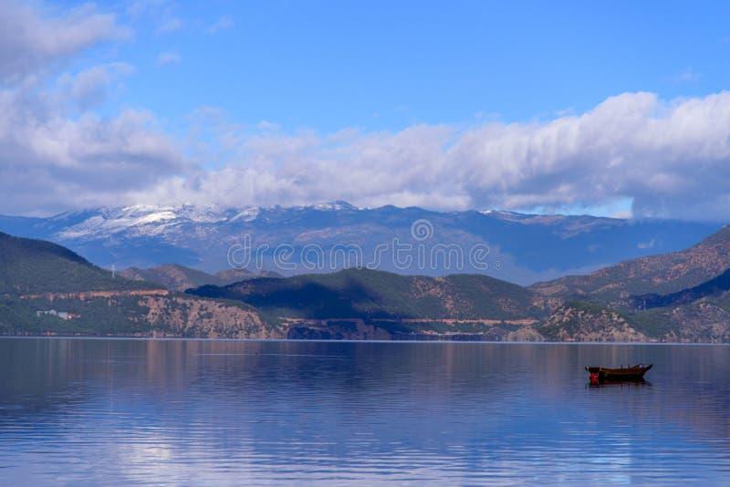 Una barca che galleggia sul lago immagini stock