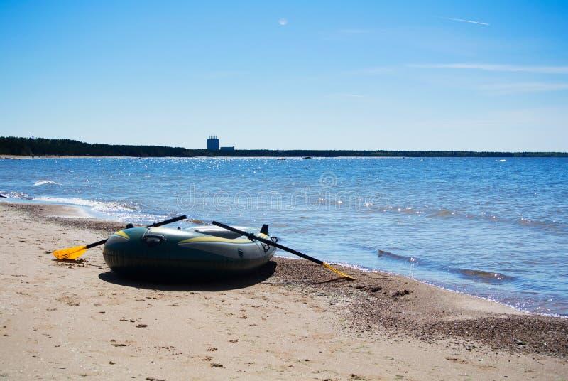 Una barca gonfiabile alla mattina in anticipo della molla sulla costa del Mar Baltico fotografie stock libere da diritti