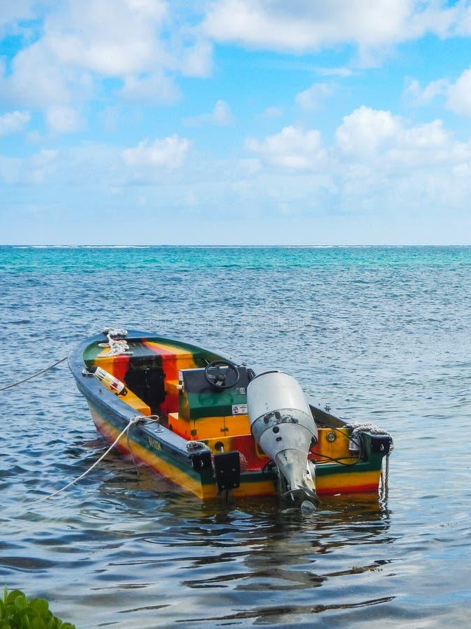 Una barca variopinta galleggia in acqua bassa nel mare caraibico fotografia stock