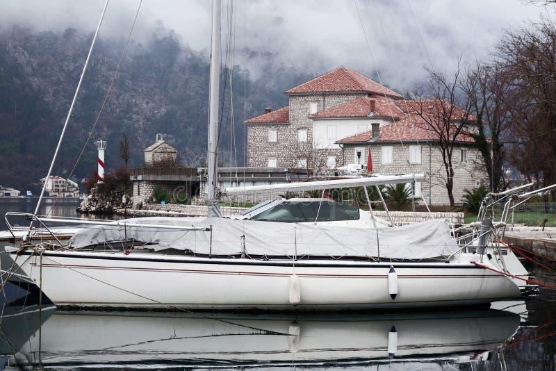 Una barca a vela al pilastro, una casa di pietra sulla riva e un faro nella baia Montagne in nebbia fotografia stock libera da diritti