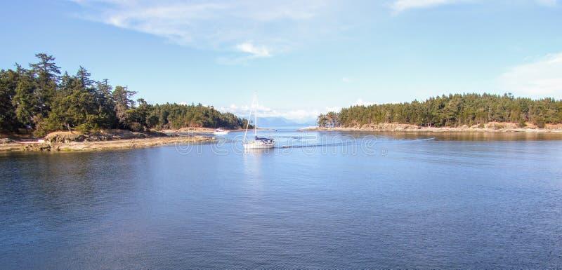 Una barca a vela di medie dimensioni che naviga da solo attraverso l'oceano completamente calmo e dopo alcune piccole isole un be immagini stock libere da diritti