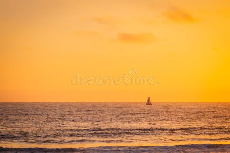Una barca a vela naviga attraverso l'orizzonte del cielo e del mare d'ardore fotografia stock