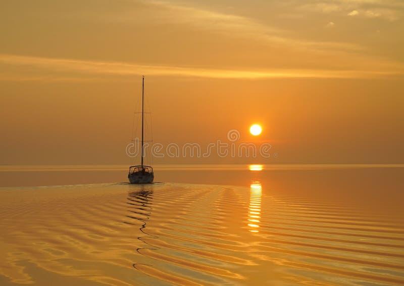 Una barca a vela parte un ancoraggio calmo nell'sunris gialli luminosi immagini stock