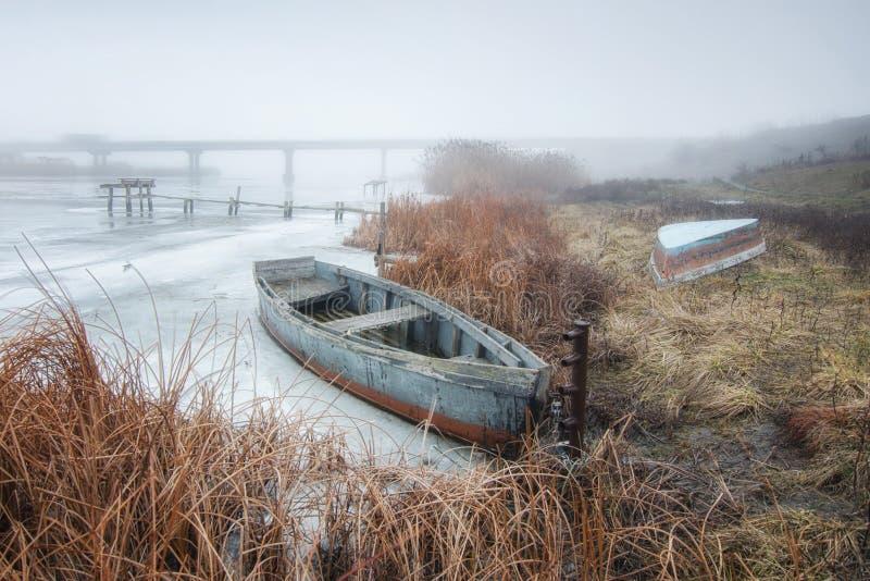 Una barca vuota sta trovandosi sulla sponda del fiume nell'inverno immagini stock libere da diritti