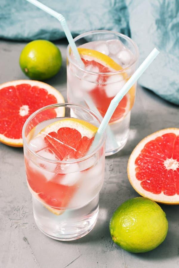 Una bebida de enfriamiento de la fruta cítrica con el pomelo y el hielo en un vidrio en un fondo concreto gris foto de archivo libre de regalías
