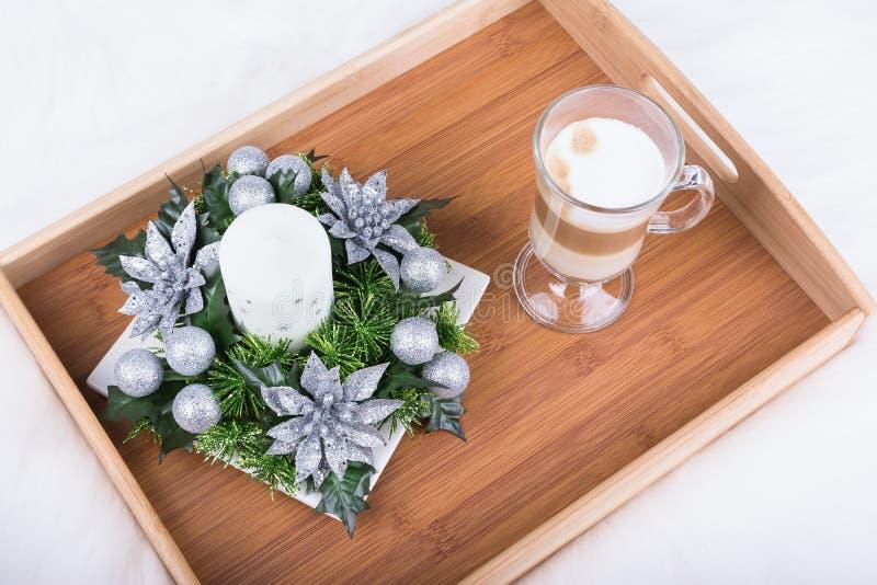 Una bebida del capuchino y una decoración de la Navidad con la vela, la rama del abeto y las bolas de la plata en la alfombra pel imagen de archivo