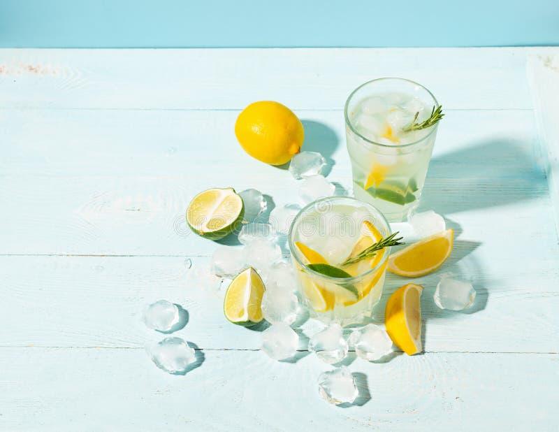 Una bebida del limón y de la cal en un vidrio elegante en un fondo azul con sol brillante Cóctel o mojito del verano fotos de archivo libres de regalías