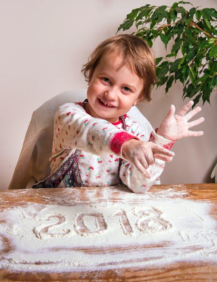 Una bella bambina si rallegra vicino all'iscrizione di 2018 sopra fotografie stock libere da diritti