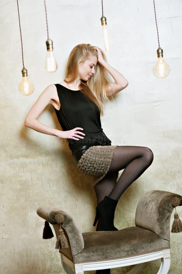 Una bella bionda attraente, una ragazza in una maglietta ondulata nera e una breve gonna grigia contro lo sfondo della a fotografia stock
