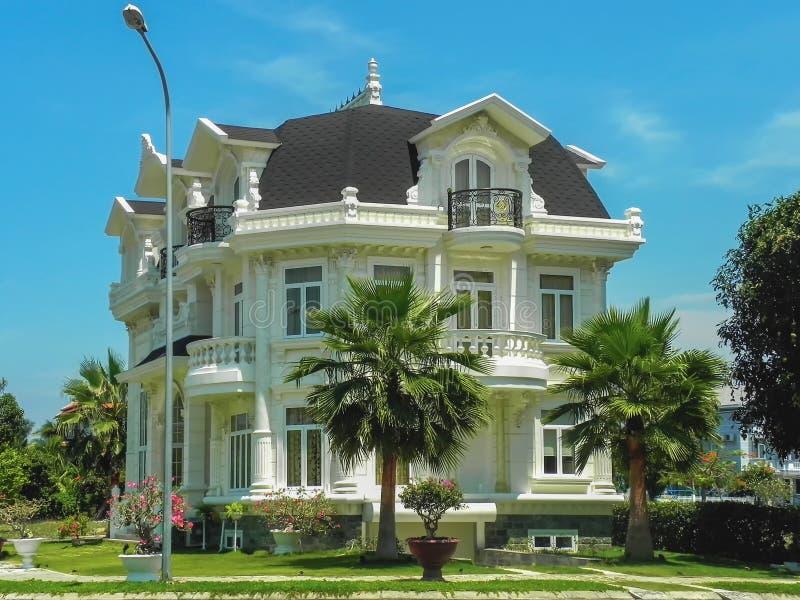 Una bella casa a tre piani con le palme, gli alberi e l'architettura del p?saggio di estate fotografia stock