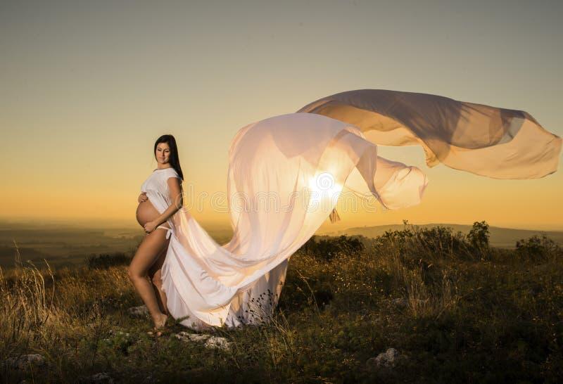 Una bella condizione vestita bianca incinta della donna al tramonto fotografie stock