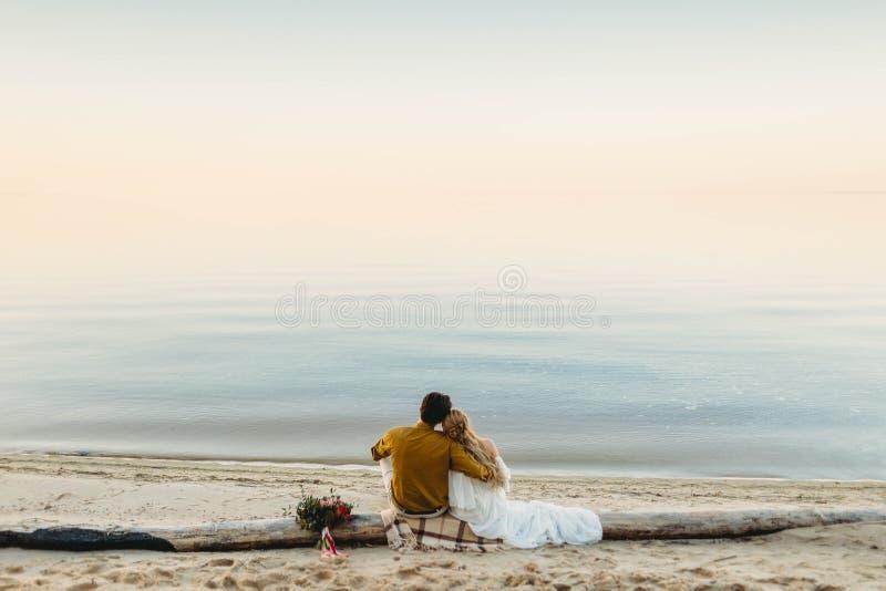 Una bella coppia sta sedendosi sul ceppo e sullo sguardo al mare Data romantica sulla spiaggia Vista dalla parte posteriore nozze fotografie stock libere da diritti