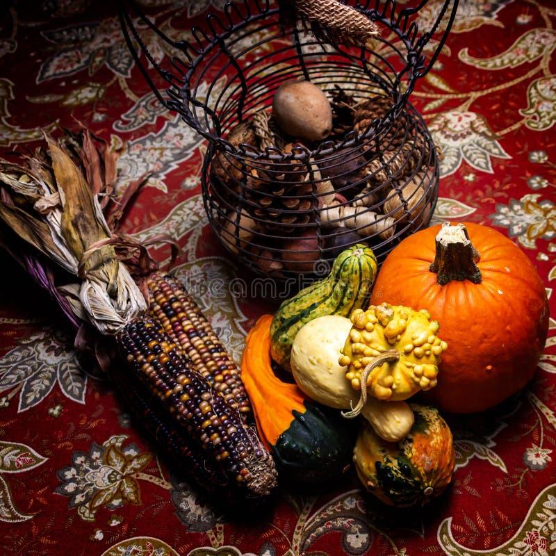 Una bella disposizione di granoturco vitreo, zucche variopinte e zucca e una zucca arancio su una tovaglia variopinta in autunno fotografia stock libera da diritti