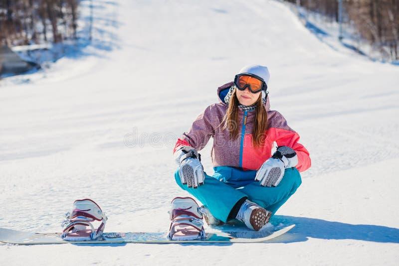 Una bella donna in abbigliamento per lo snowboard che si siede sulla pista per lo snowboard fotografia stock libera da diritti