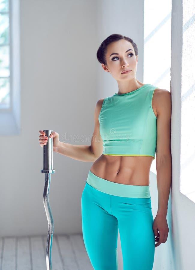 Una bella donna in abiti sportivi che tengono un bilanciere mentre guardando lateralmente e appoggiandosi una parete nella palest immagini stock libere da diritti