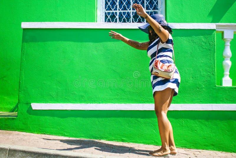 Una bella donna africana in un vestito a strisce blu e bianco che balla davanti BO-Kaap ad una casa tradizionale con le pareti ve fotografia stock libera da diritti