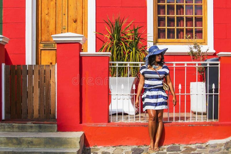 Una bella donna africana in un vestito a strisce blu e bianco che fa un giro turistico nella zona delle case tradizionali della B immagine stock libera da diritti