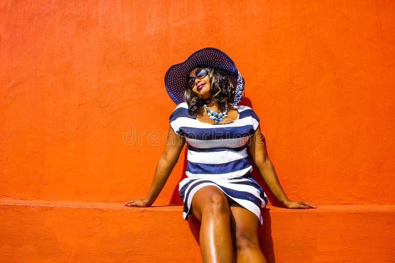 Una bella donna africana in un vestito a strisce blu e bianco che modella davanti ad una casa tradizionale BO-Kaap con le pareti  immagini stock
