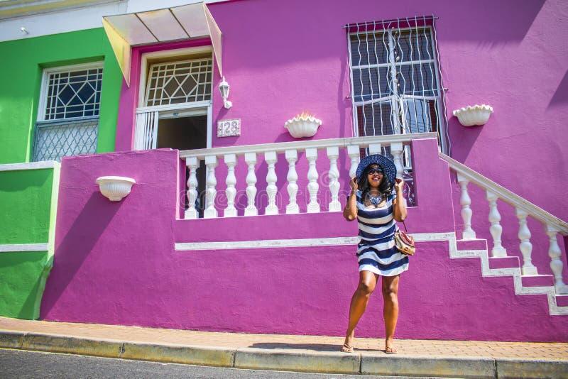 Una bella donna africana in un vestito a strisce blu e bianco che modella davanti ad una casa tradizionale con le pareti rosa La  fotografia stock