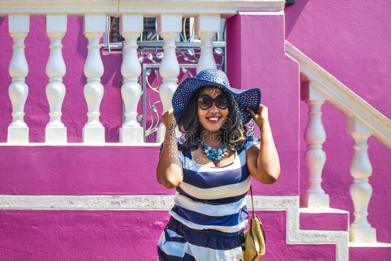 Una bella donna africana in un vestito a strisce blu e bianco che modella davanti ad una casa tradizionale con le pareti rosa La  fotografie stock