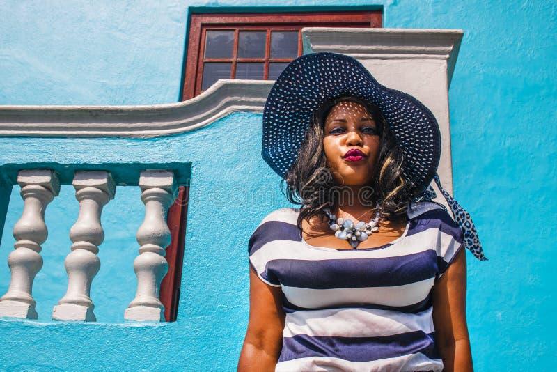 Una bella donna africana in un vestito a strisce blu e bianco che modella davanti BO-Kaap ad una casa tradizionale con le pareti  immagini stock libere da diritti