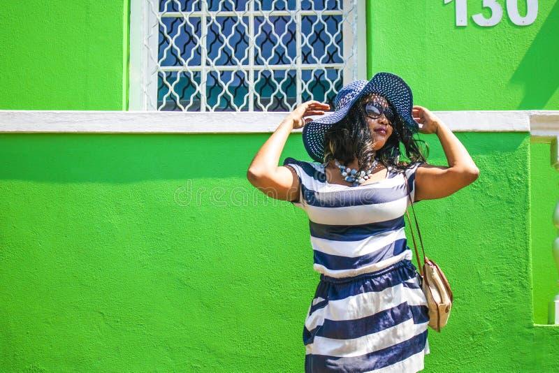 Una bella donna africana in un vestito a strisce blu e bianco che modella davanti BO-Kaap ad una casa tradizionale con le pareti  fotografia stock