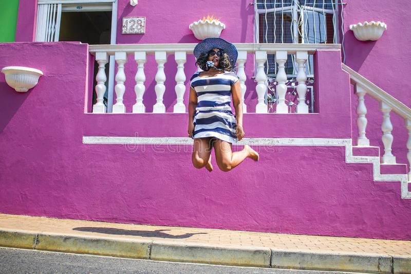 Una bella donna africana in un vestito a strisce blu e bianco che salta davanti ad una casa tradizionale con le pareti rosa La BO immagine stock libera da diritti