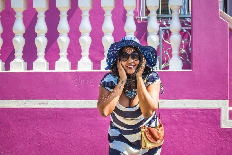 Una bella donna africana in un vestito a strisce blu e bianco che sorride davanti ad una casa tradizionale con le pareti rosa La  fotografia stock