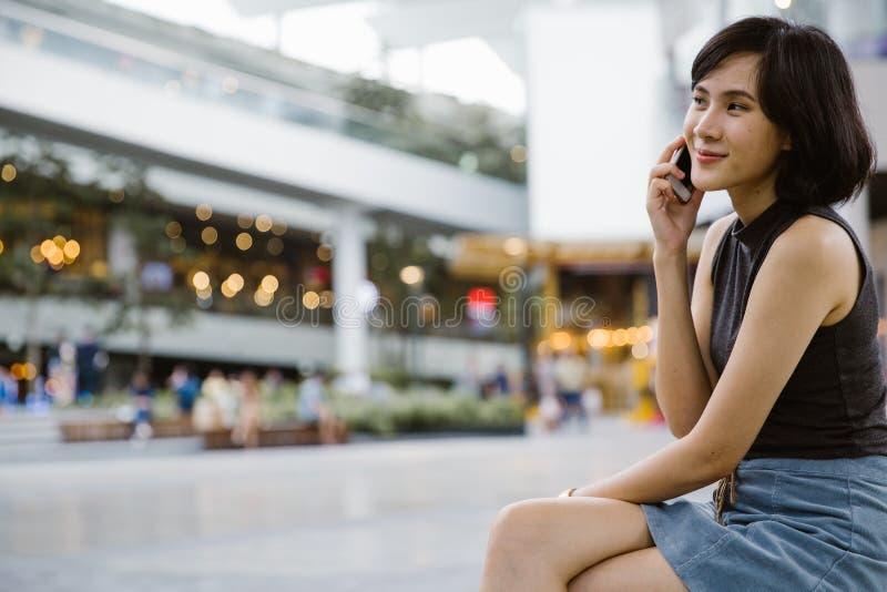 Una bella donna asiatica attraente che per mezzo del telefono di mobil agli sms fotografia stock