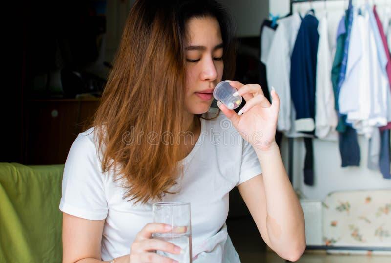 Una bella donna asiatica prende medicine e acqua potabile fotografie stock