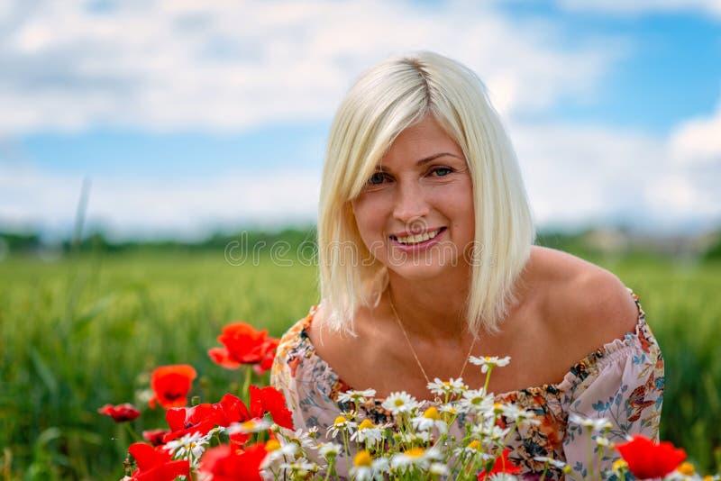 Una bella, donna attraente e bionda raccoglie i fiori del prato sull'orlo del campo Fuoco molle fotografia stock libera da diritti