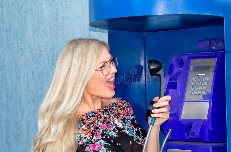 Una bella donna bionda che wiaring i vetri sta tenendo un ricevitore telefonico in un telefono a gettone Emozionalmente grida nel fotografie stock