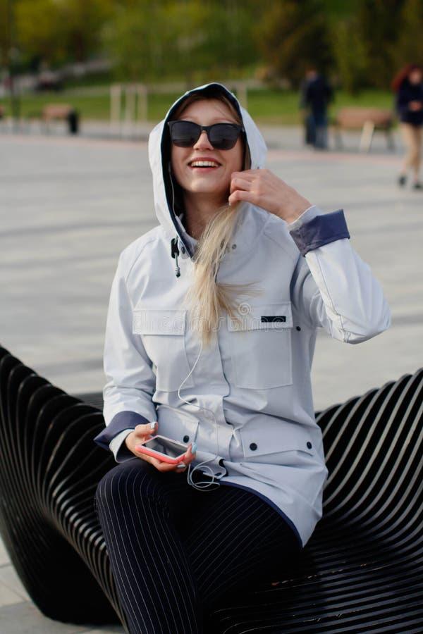 Una bella donna bionda sta ascoltando musica sul suo smartphone mentre si sedeva su un banco in un parco della citt? fotografie stock libere da diritti