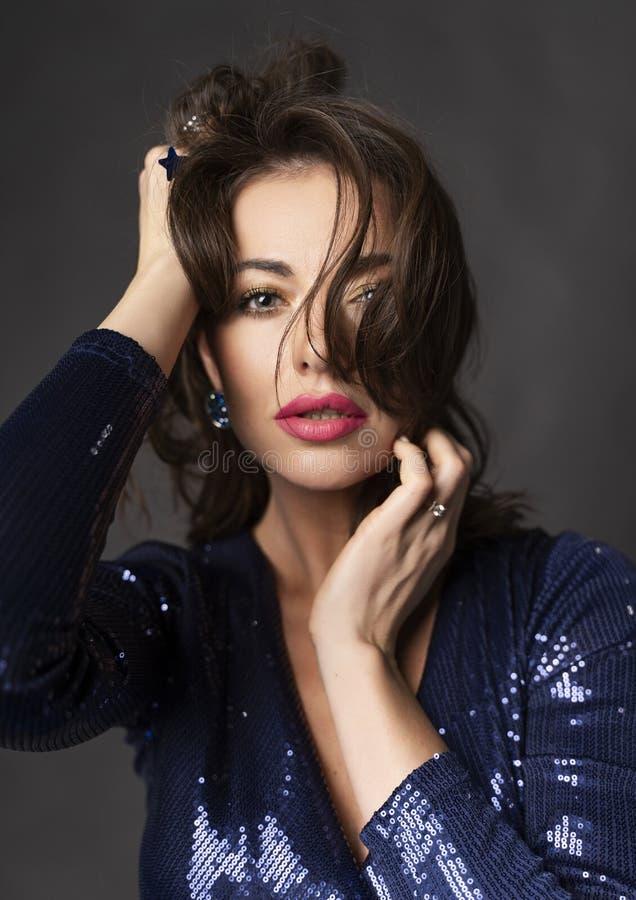 Una bella donna castana che porta un vestito blu luccicante contro un fondo grigio sensuale tocca i suoi capelli ed affronta lei fotografia stock