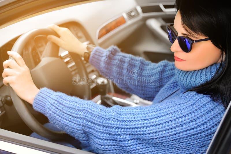 Una bella donna castana graziosa in maglione blu ed occhiali da sole sta conducendo un'automobile modificato fotografie stock libere da diritti