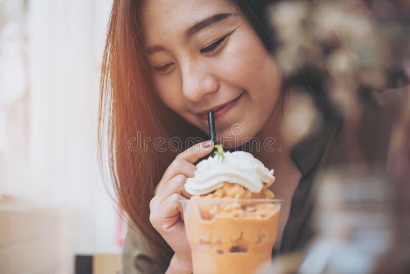 Una bella donna che beve frappè tailandese del tè e panna montata sulla cima con paglia immagini stock