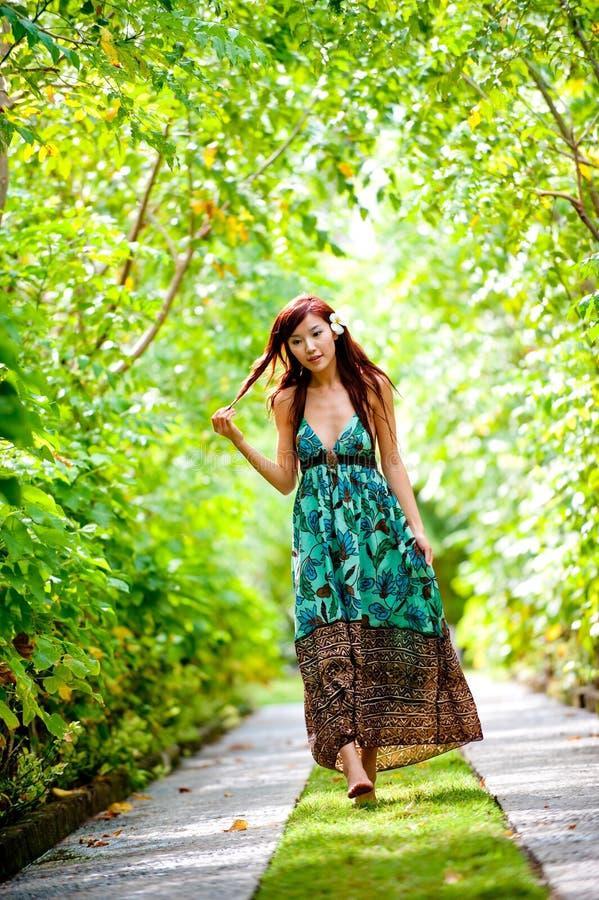 Una bella donna che cammina attraverso il ricorso fotografie stock