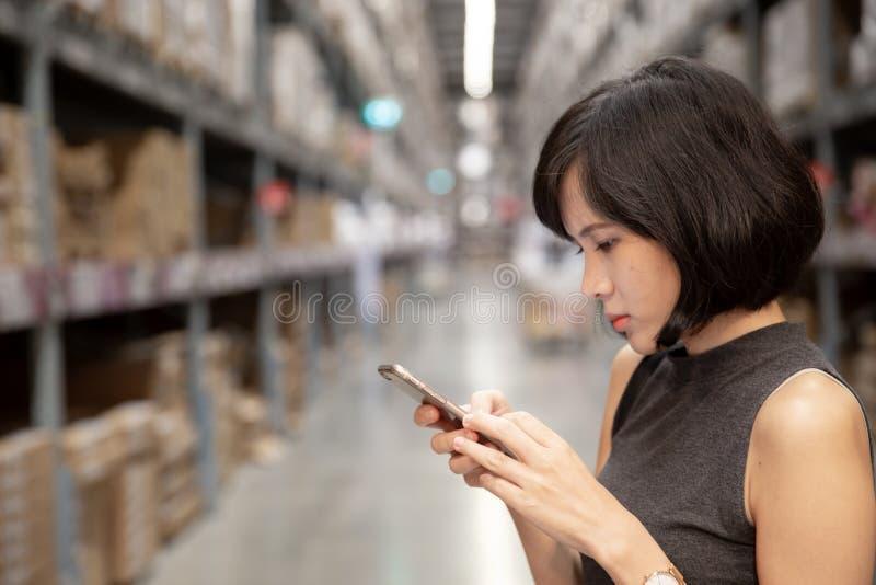 Una bella donna che per mezzo dello Smart Phone al magazzino fotografie stock