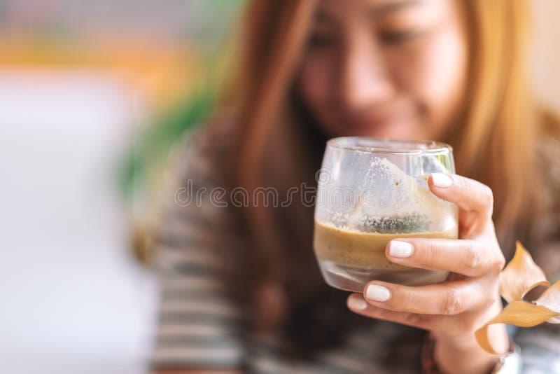 Una bella donna che tiene un vetro di caffè ghiacciato per bere in caffè fotografia stock