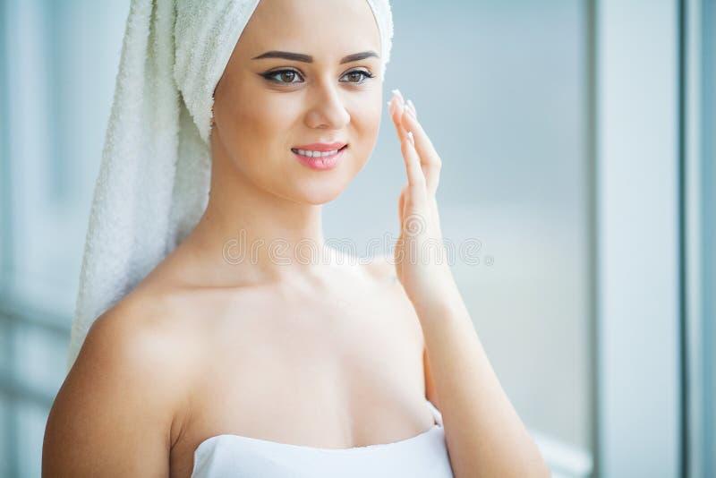 Una bella donna che usando un prodotto di cura di pelle, un idratante o una lozione e uno Skincare prendenti cura della sua carna fotografia stock