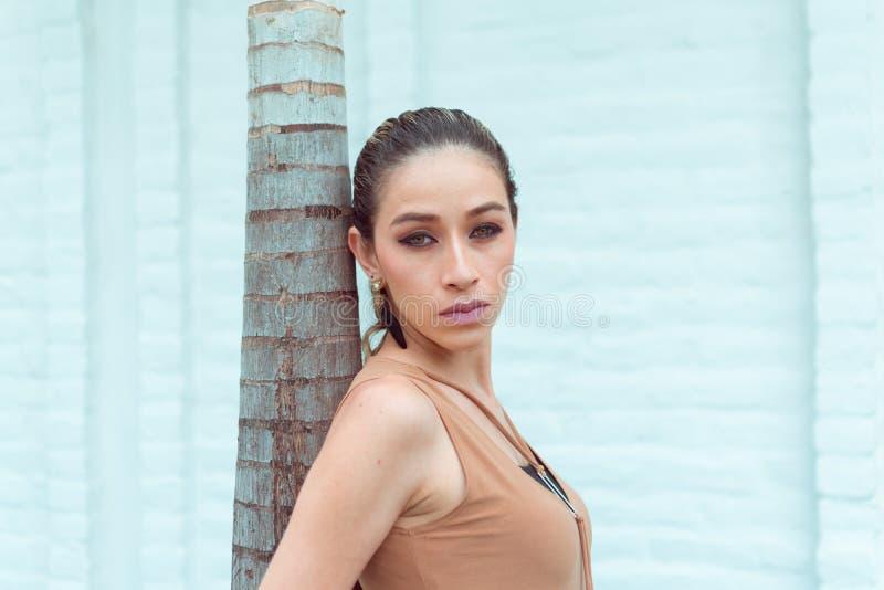 Una bella donna esile che riposa su una palma che fissa alla macchina fotografica, fa fotografare gli occhi verdi e buon il trucc immagini stock